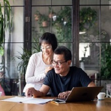 Senior Chinese couple talking about home finances.