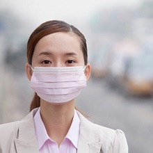 Chinese woman wearing face mask because of air pollution in the city