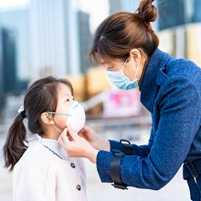 Asian woman and her daughter wearing masks in city street